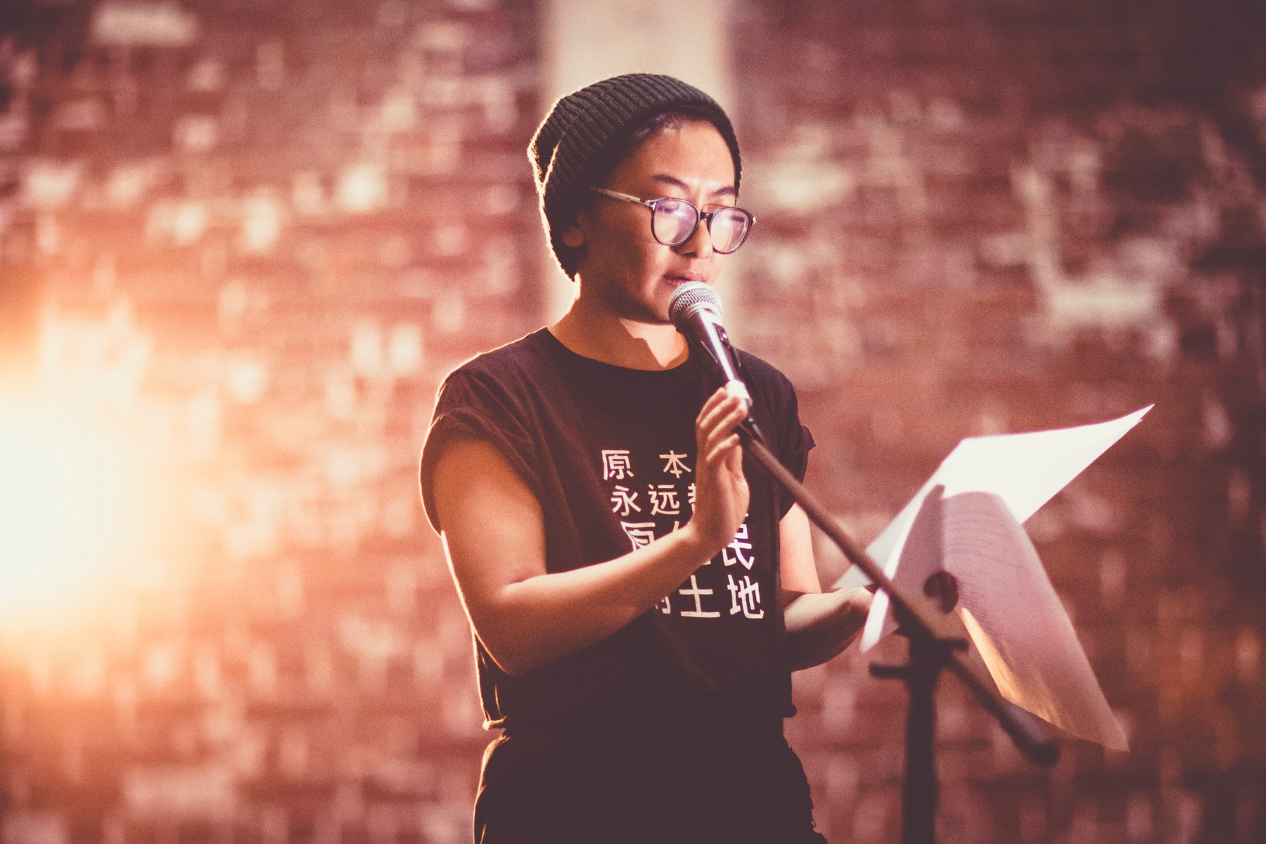 A person in a beanie and glasses reading behind a microphone.