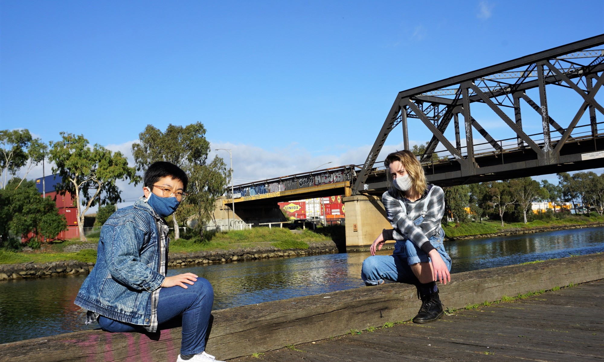 Two friends, wearing face masks, in an industrial landscape with a river and bridge behind them.