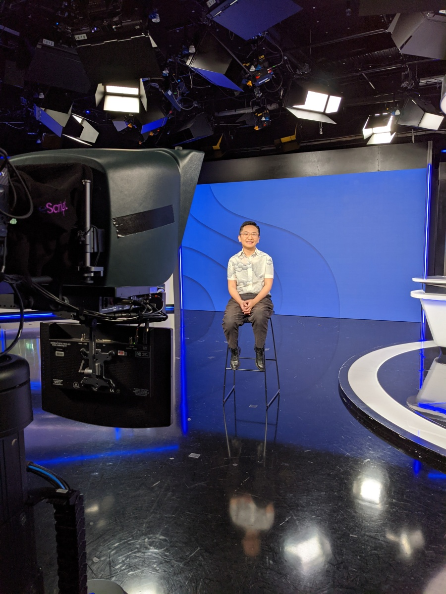 Jinghua in a white shirt and black pants, sitting on a high stool on a tv set with a blue background and a camera in the foreground.