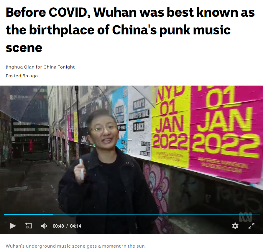 Screenshot of video with Jinghua standing in a laneway papered with gig posters. The headline says 'Before Covid, Wuhan was best known as the birthplace of China's punk music scene.'